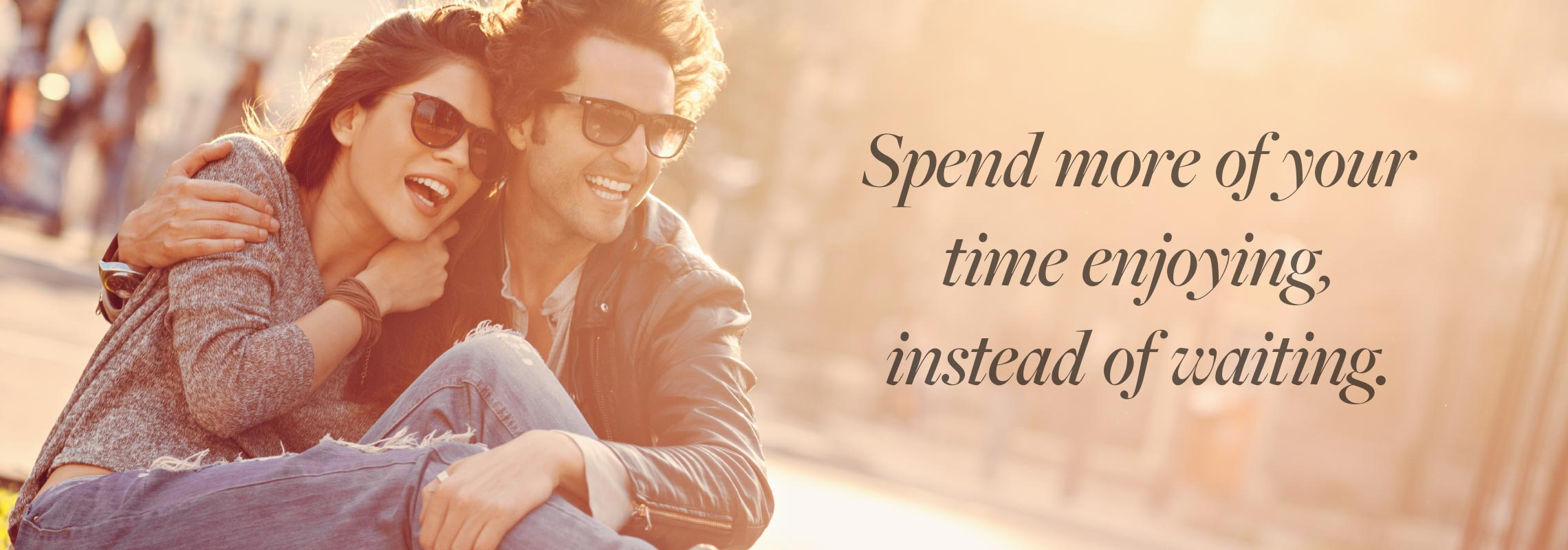 Happy, young couple enjoying the outdoors in the sun, wearing glasses that have photochromic lenses that get darker in the sunlight with the statement on the image; Spend more of your time enjoying, instead of waiting.