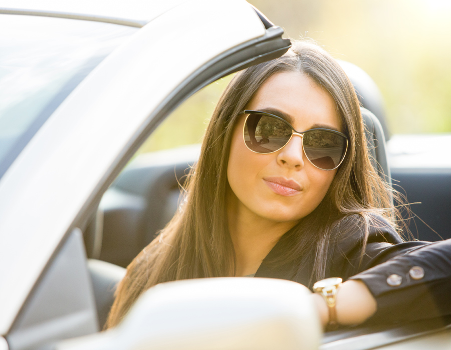Woman sitting in a convertible car wearing glasses that have photochromic lenses that get darker in sunlight